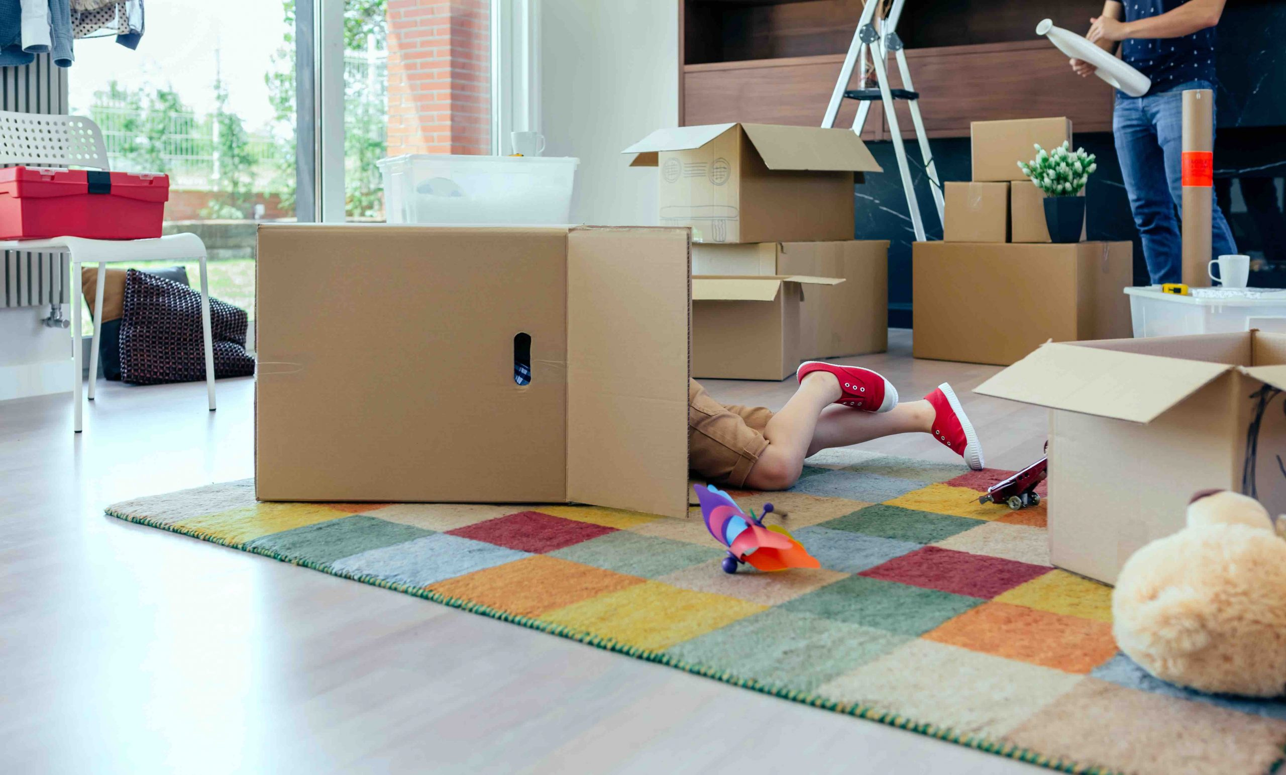 Little boy playing inside a moving box while his father unpacks in the living room