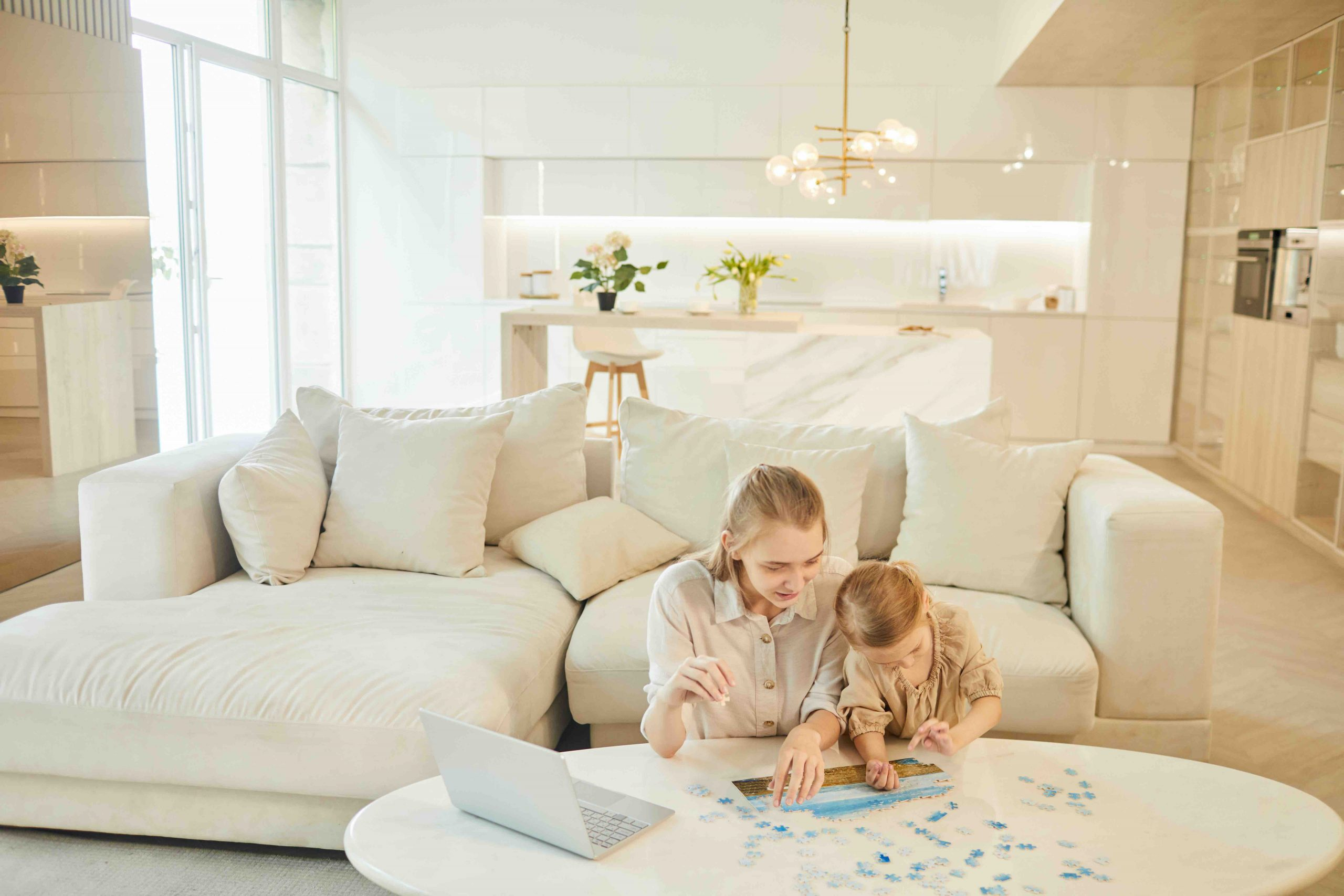 Warm-toned wide angle portrait of two sisters solving puzzle together while enjoying time at home indoors in minimal white interior, copy space